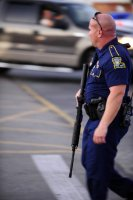 Advocate staff photo by LESLIE WESTBROOK -- A Louisiana State Trooper responds to the scene of a shooting at the Grand 16 movie theater Thursday, July 23, 2015, in Lafayette, La. Multiple injuries are reported and the shooter is presumed dead.